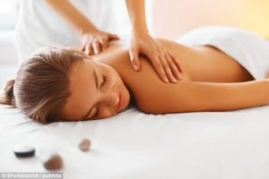Woman receiving a massage on her back to relieve pain